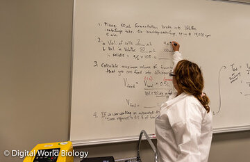 Woman in lab coat writing on white board